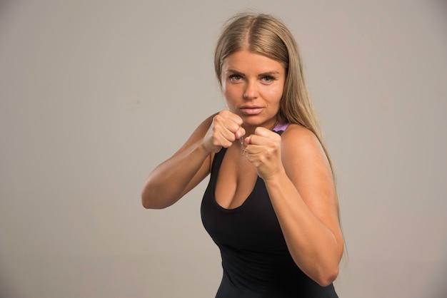 Vrouwelijk model in sportbeha die bokstrucs doet.