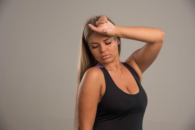 Vrouwelijk model in sportbeha houdt haar hoofd vast.