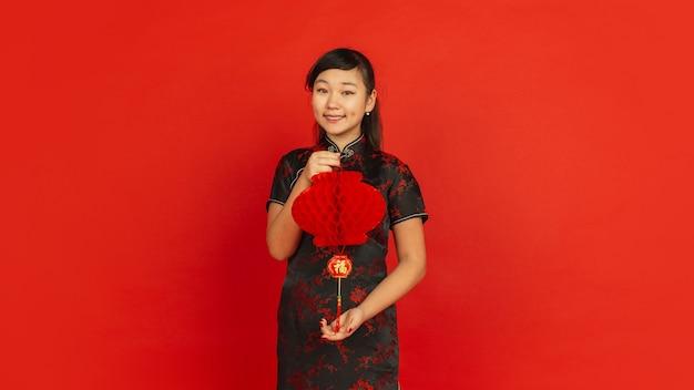 Vrouwelijk model in traditionele kleding ziet er gelukkig uit en lacht met decoratie Gratis Foto