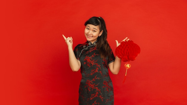 Vrouwelijk model in traditionele kleding ziet er gelukkig uit en lacht met decoratie