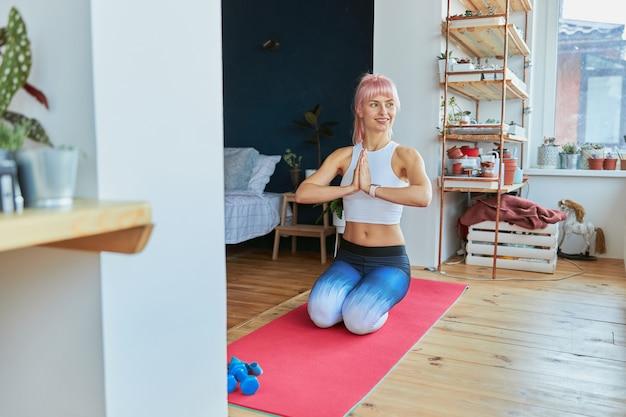 Vrouwelijk model in trainingspak houdt handen in namaste mudra zittend op knieën op mat