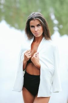 Vrouwelijk model in witte blazer en zwembroek in het meer