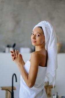 Vrouwelijk model in witte handdoek. vrouwen, schoonheid en hygiëne concept.
