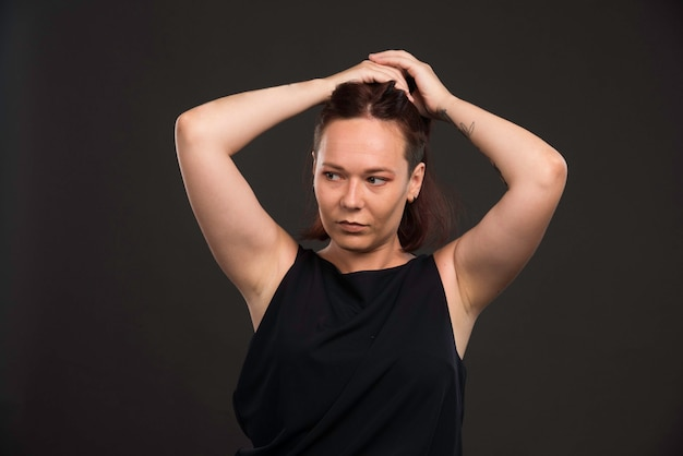 Vrouwelijk model in zwart overhemd dat haren verzamelt.