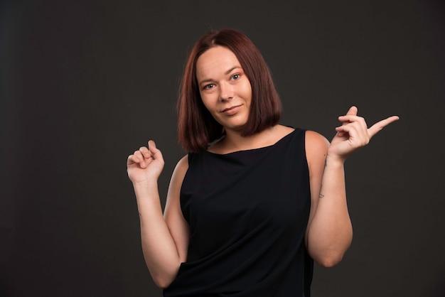 Vrouwelijk model in zwart overhemd dat op iets richt.