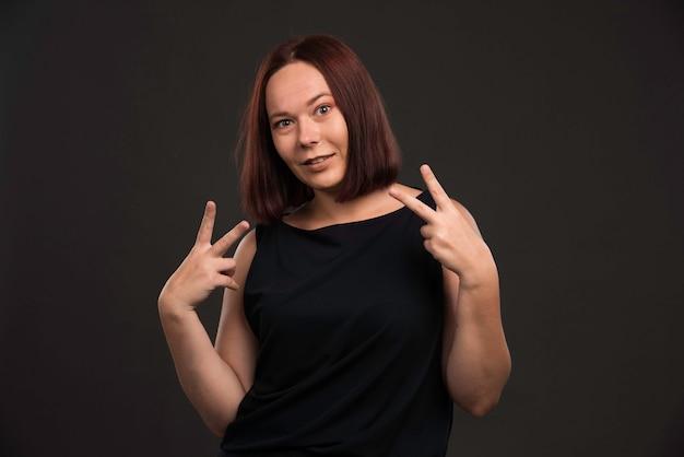 Vrouwelijk model in zwart overhemd vredesbericht verzenden.