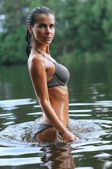 Vrouwelijk model in zwarte zwembroek in het meer