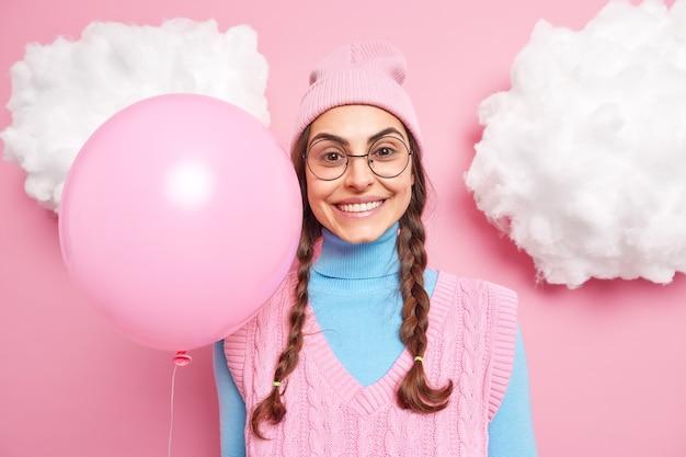Vrouwelijk model lacht vrolijk gekleed in vrijetijdskleding heeft twee gekamde lange staartjes draagt een ronde bril houdt een opgeblazen ballon vast anticipeert op vakantie of wanneer het feest begint