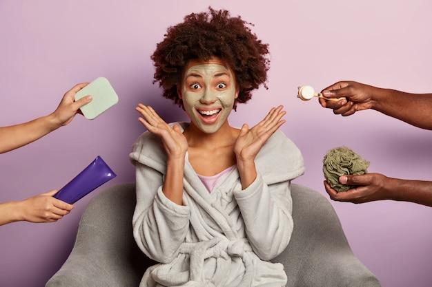 Vrouwelijk model met donkere huid heeft een onberispelijke huid, past een kleimasker toe op het gezicht