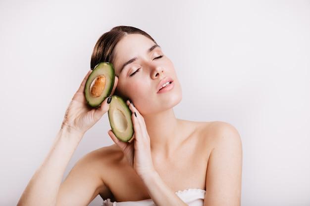 Vrouwelijk model met heldere huid geïnspireerd poseren op geïsoleerde muur met voedzame, gezonde avocado's.