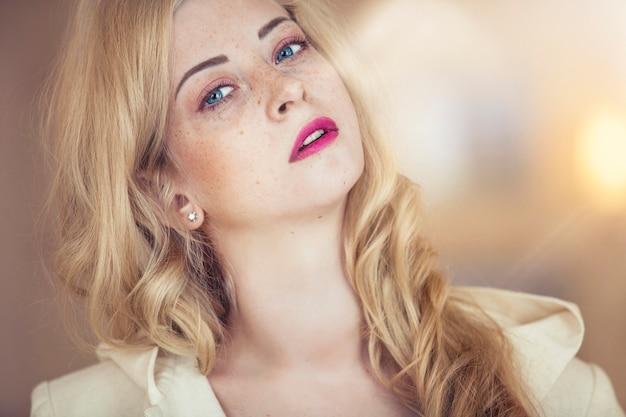 Vrouwelijk model met sproeten op haar gezicht met het heldere roze portret van de lippenclose-up