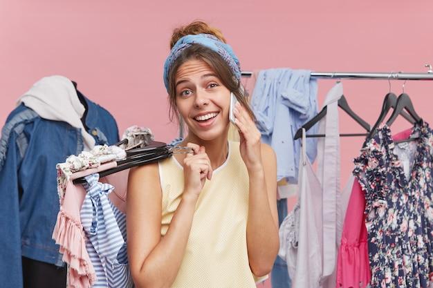Vrouwelijk model pronkt met haar nieuwe aankopen, belt haar beste vriendin terwijl ze hangers vasthoudt met kleren in het warenhuis of in de paskamer. positieve vrouw die op celtelefoon babbelt en het winkelen doet