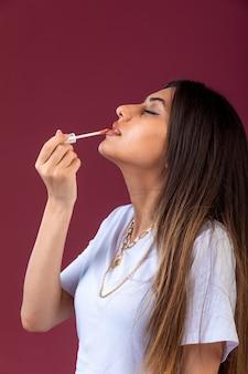 Vrouwelijk model roze lippenstift op rood oppervlak toe te passen