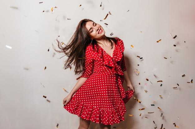 Vrouwelijk model sloot haar ogen van plezier en dansen met een glimlach op de witte muur met vallende confetti. foto van dame in rode jurk.