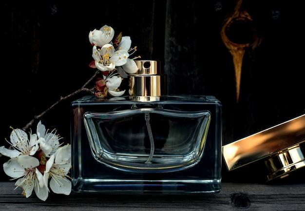 Vrouwelijk parfum met bloemen op hout