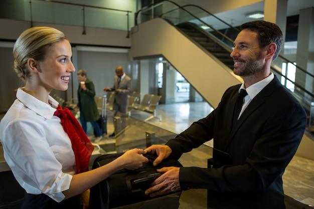 Vrouwelijk personeel bagage overhandigen aan zakenman