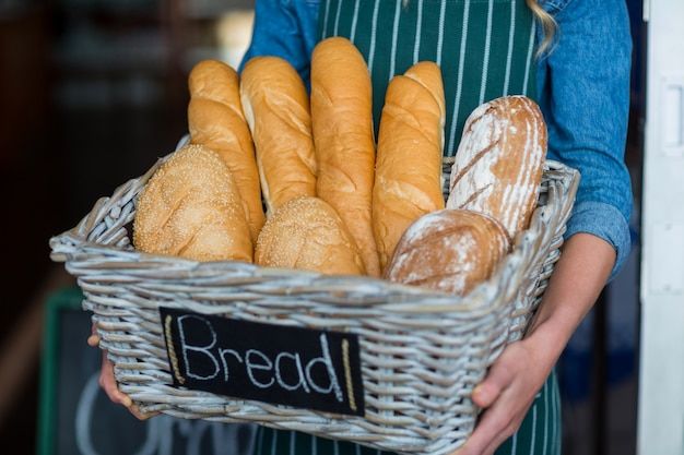 Vrouwelijk personeel dat een mand brood houdt