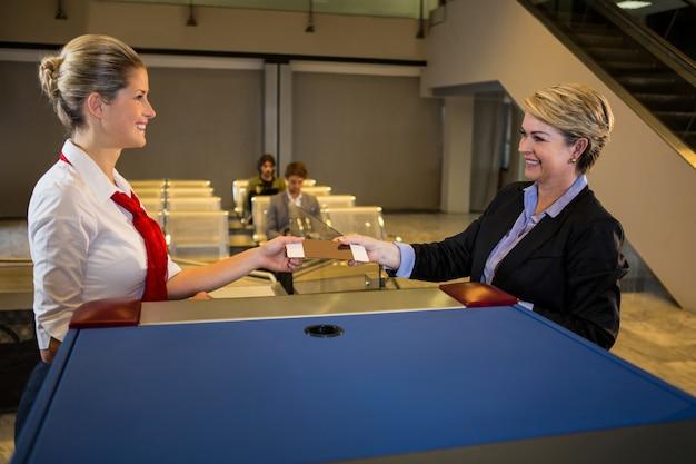 Vrouwelijk personeel dat instapkaart geeft aan de onderneemster bij teller