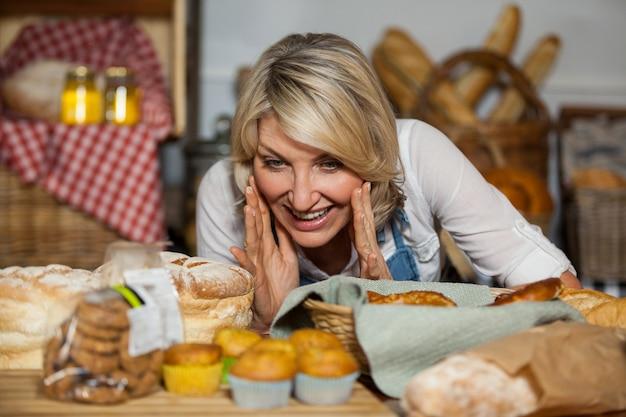 Vrouwelijk personeel dat verschillende zoete gerechten bekijkt