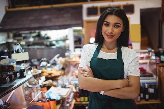 Vrouwelijk personeel dat zich met wapens bevindt die in supermarkt worden gekruist