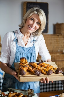 Vrouwelijk personeel dat zoet voedsel in bakkerijsectie houdt