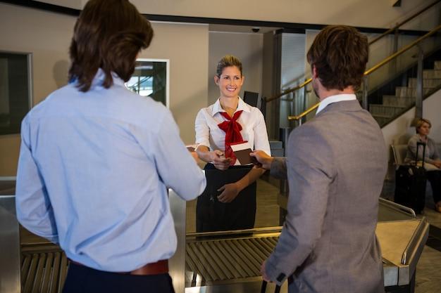 Vrouwelijk personeel die instapkaart van passagiers controleren bij incheckbalie