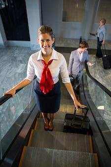Vrouwelijk personeel en passagiers met bagage op roltrap