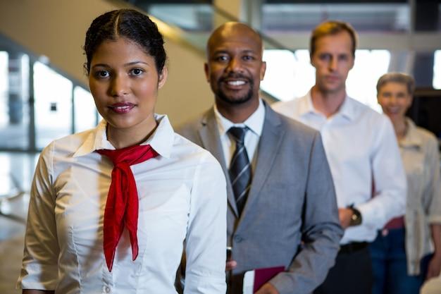 Vrouwelijk personeel en passagiers staan in de luchthaventerminal