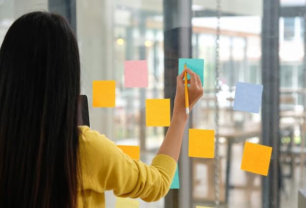 Vrouwelijk personeel gebruikt een pen om een papernote op het glas te schrijven om hun werk te plannen.