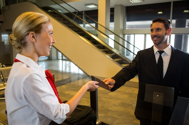 Vrouwelijk personeel geeft instapkaart aan de passagier