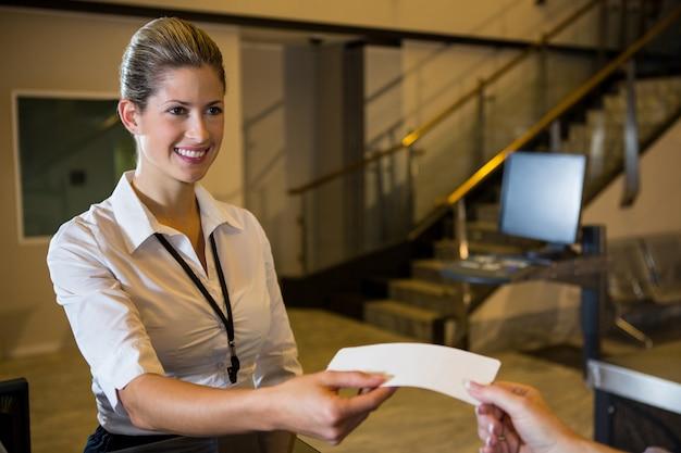 Vrouwelijk personeel kaartje geven aan passagier