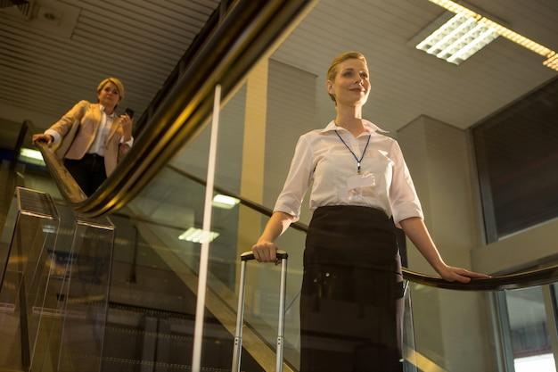 Vrouwelijk personeel komt van de roltrap
