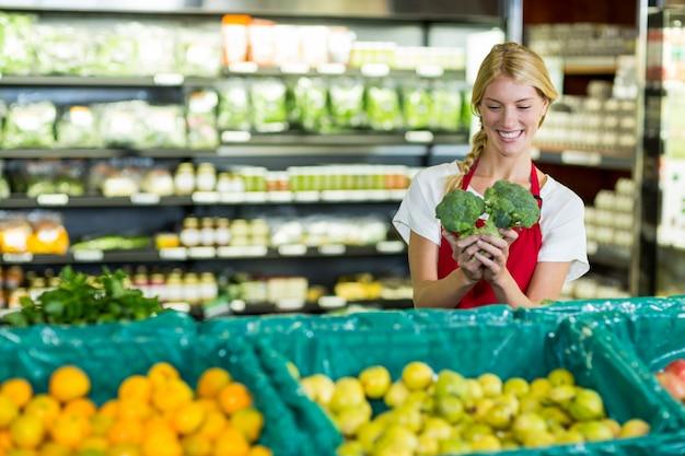 Vrouwelijk personeel met broccoli in biologische sectie
