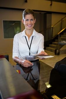 Vrouwelijk personeel met instapkaart aan balie