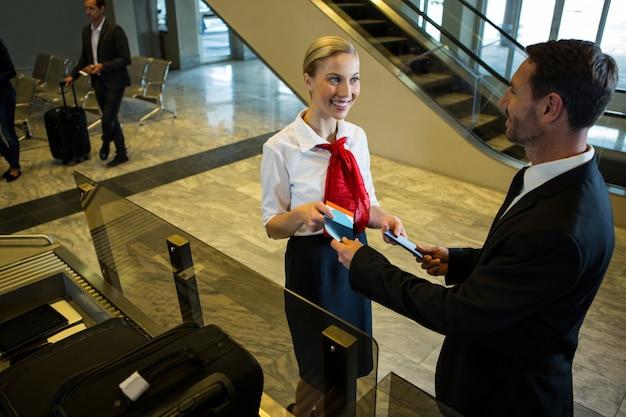 Vrouwelijk personeel overhandigt instapkaart en paspoort