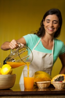Vrouwelijk personeel sap gieten in glas aan balie