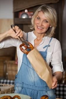 Vrouwelijk personeel zoet voedsel in een papieren zak verpakken