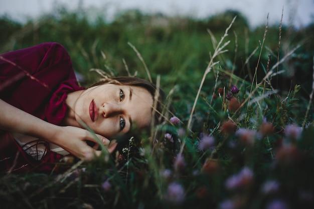 Vrouwelijk portret. charmante vrouw in violet shirt ligt op de gree