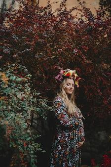 Vrouwelijk portret. de charmante zwangere vrouw in bloemkleding stelt