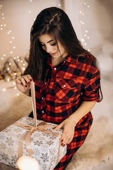 Vrouwelijk portret. de zwangere vrouw in gecontroleerd overhemd stelt in comfortabele ruimte met kerstboom en opent pr