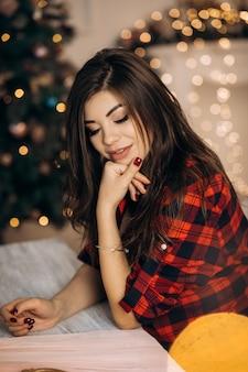 Vrouwelijk portret. de zwangere vrouw in gecontroleerd overhemd stelt in comfortabele ruimte met kerstboom