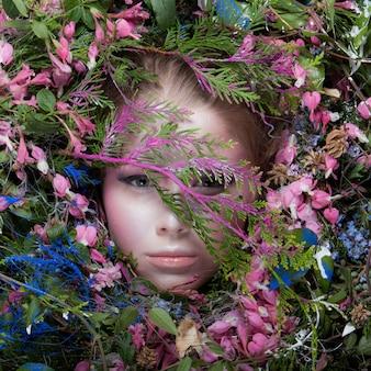 Vrouwelijk portret in sprookjesachtige stilering omringd met natuurlijke planten en bloemen.