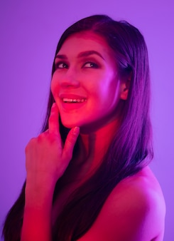 Vrouwelijk portret met roze neon op paars