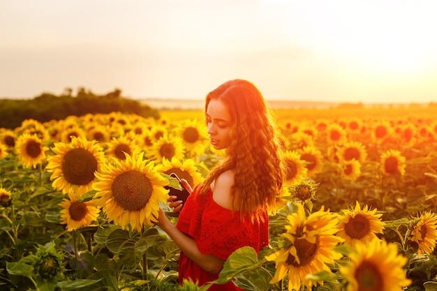 Vrouwelijk portret van jonge vrouw op gebied van bloeiende zonnebloemen in stralen van zonsondergang schattig meisje van cauca...