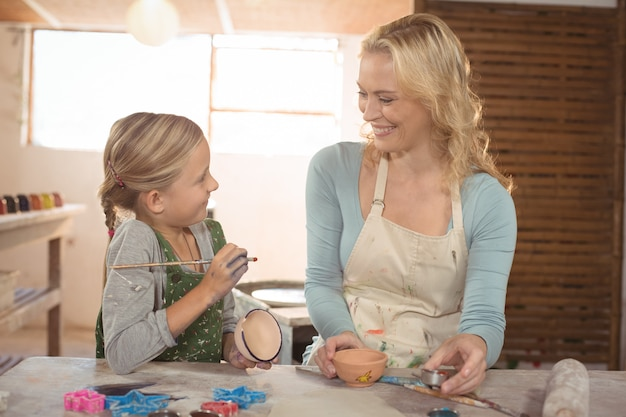 Vrouwelijk pottenbakkers bijwonend meisje in het schilderen