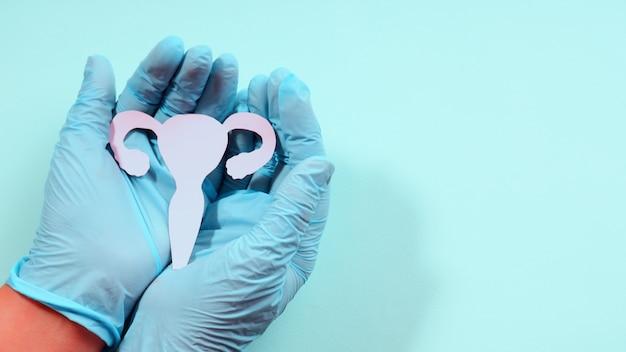 Vrouwelijk reproductief gezondheidsconcept. hand met baarmoeder vorm gemaakt van papier op roze achtergrond. bewustwording van baarmoederaandoeningen zoals endometriose, pcos, soa's of gynaecologische kanker.