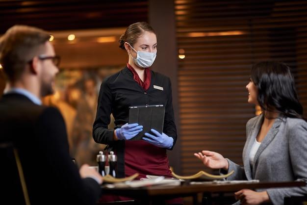 Vrouwelijk restaurantpersoneel aan tafel met twee personen