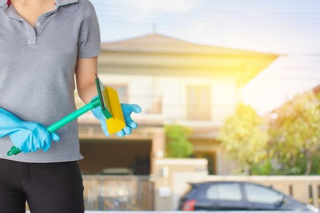 Vrouwelijk schoonmakend personeel in huis vage achtergrond