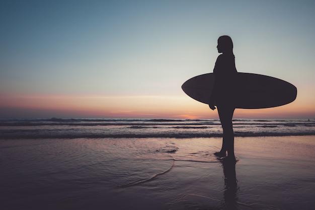 Vrouwelijk silhouet met surfplank op het strand bij zonsondergang