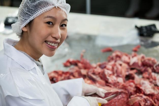 Vrouwelijk slager scherp vlees bij vleesfabriek